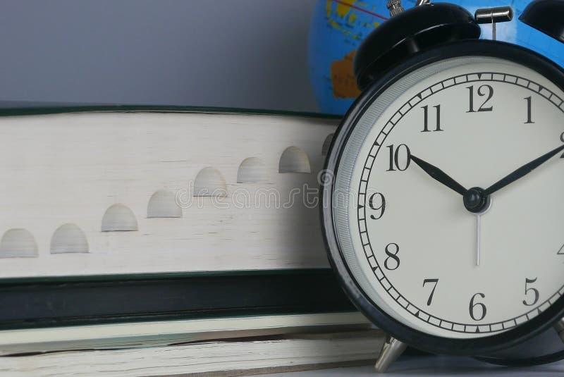 Stapel van boek met bol en klok Onderwijs, tijd en wereldconcept royalty-vrije stock afbeelding