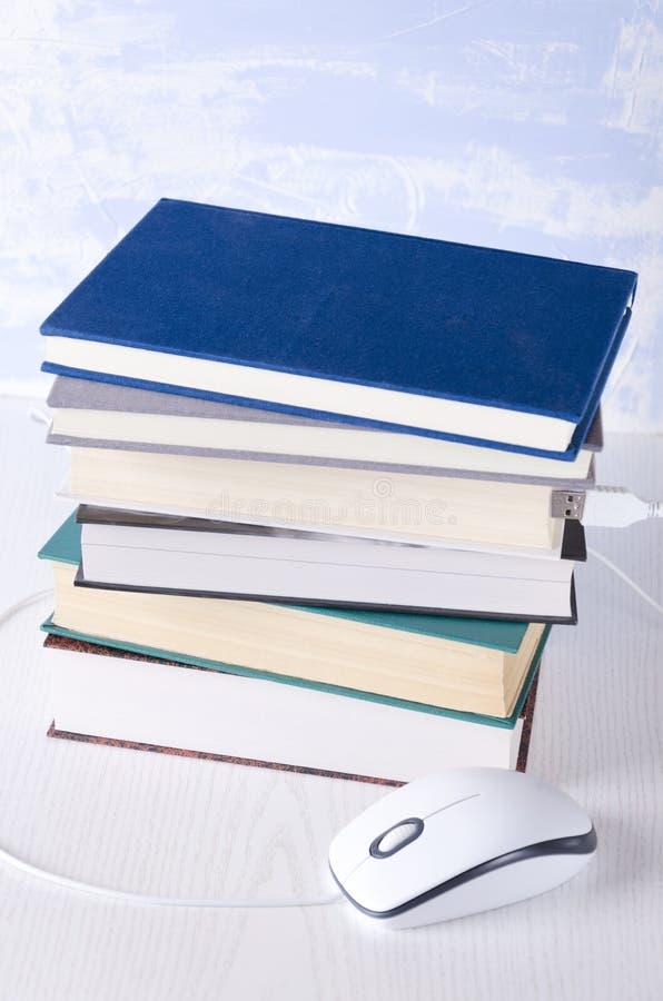 Stapel van boeken en computermuis op de witte lijst Concept online onderwijs en vrije lezing stock afbeeldingen