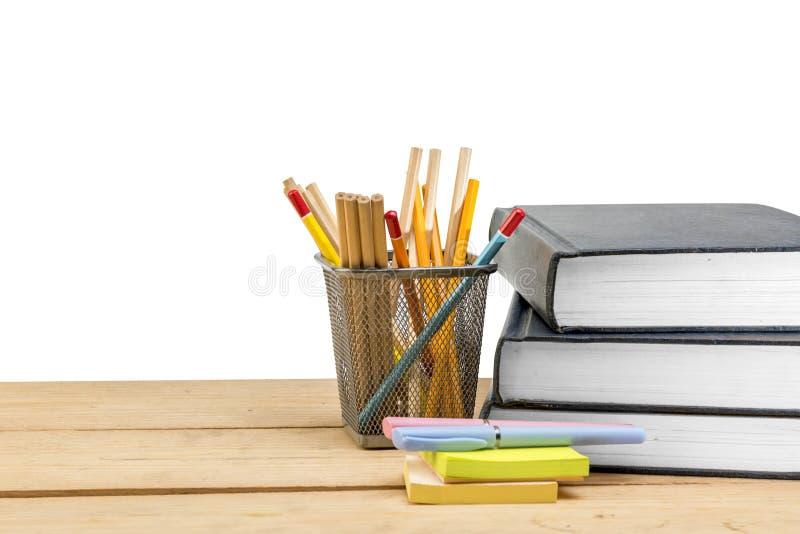 Stapel van boeken met nota'sdocument en pen met potloden in mandcontainer op houten lijst stock afbeeldingen