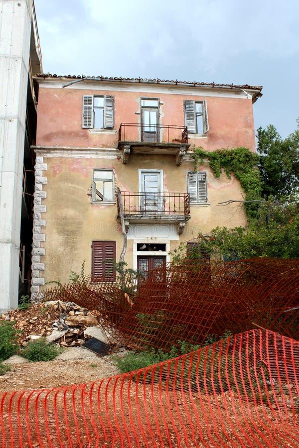 Stapel van bouwmateriaal en geroest metaal voor lang verlaten oud die flatgebouw voor het vernietigen met gebroken wordt geplaats royalty-vrije stock foto's