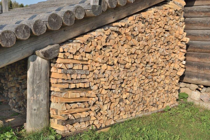 Stapel van brandhout bij de muur van het huis stock afbeelding