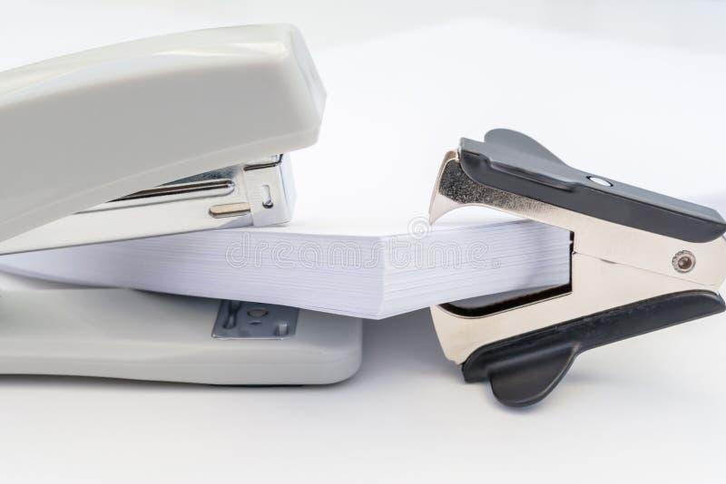 Stapel van bureaudocument, zwart voornaamste vlekkenmiddel en grijze nietmachine op witte achtergrond, concepten abstracte achter stock afbeelding