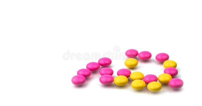 Stapel van de roze en gele ronde pillen van suikerdragees op witte achtergrond met exemplaarruimte Kleurrijke pillen royalty-vrije stock fotografie