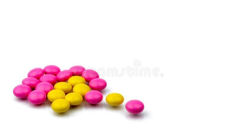 Stapel van de roze en gele ronde pillen van suikerdragees op witte achtergrond met exemplaarruimte Kleurrijke pillen stock foto