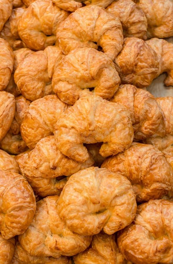 Stapel van de verse gebakken mouthwatering gebakjes van het amandelcroissant in de mand Verse gebakken croissanten Een stapel van royalty-vrije stock afbeelding