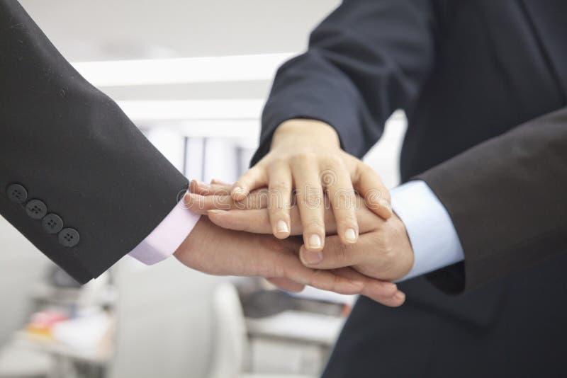 Stapel van drie bedrijfsmensenhanden samen voor een toejuiching, close-up stock afbeelding