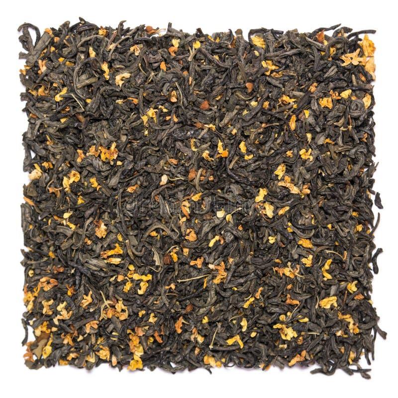 Stapel van droge groene die thee met osmanthus op witte achtergrond wordt geïsoleerd stock afbeeldingen