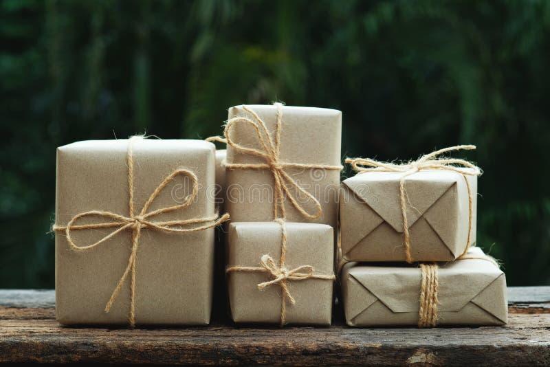 Stapel van eenvoudige het vakje van de eco vriendschappelijke gift pakketomslag met pakpapier op oude houten lijstachtergrond, gr stock fotografie