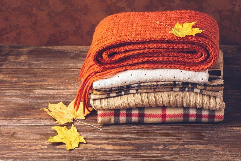 Stapel van gebreide warme kleren en de herfstbladeren op een houten achtergrond Het concept van de herfst Ge?soleerd De ruimte va royalty-vrije stock foto's