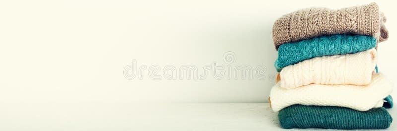 Stapel van gebreide wolsweaters op witte achtergrond met exemplaarruimte Breigoed, kleren banner stock afbeeldingen