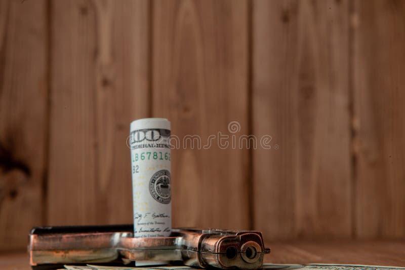 Stapel van Geld, drugsand een kanon op een houten lijst, concept over gevaar en bedreiging van de drug stock afbeeldingen