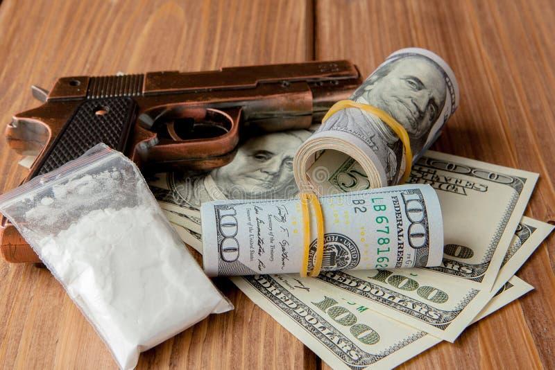 Stapel van Geld, drugsand een kanon op een houten lijst, concept over gevaar en bedreiging van de drug stock foto