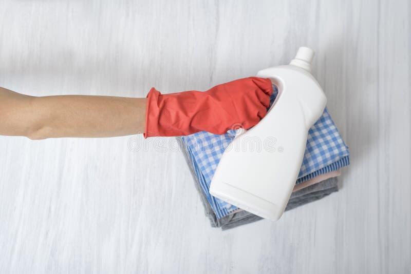 Stapel van gevouwen kleren en detergent fles in vrouwelijke hand housework stock foto's