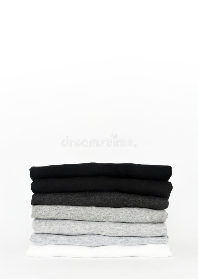 Stapel van gevouwen zwarte, grijze en witte kleuren zwart-wit t-shirt op witte achtergrond stock afbeelding