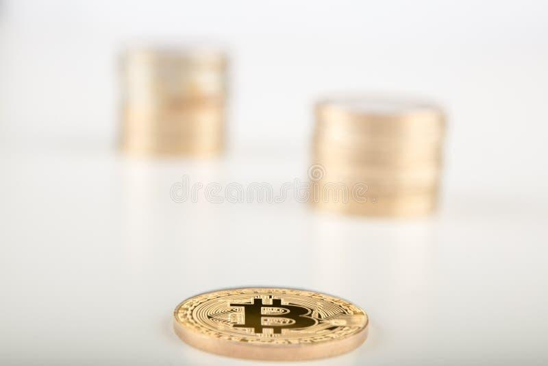 Stapel van gouden Bitcoins enig van hen die op grijze surfa leggen stock afbeelding