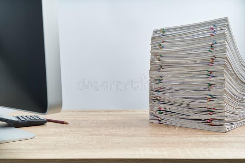 Stapel van het rapport en de computer van de overbelastingsadministratie op houten lijst royalty-vrije stock fotografie