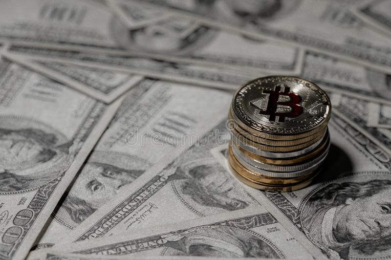 Stapel van het stapelen van Gouden bitcoin op honderd dollarsbankbiljetten enig muntstuk die de camera in scherpe nadruk onder og royalty-vrije stock afbeelding