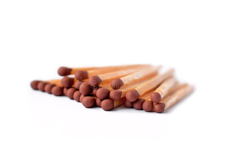 Stapel van houten matchsticks met bruine hoofden op witte achtergrond stock foto's