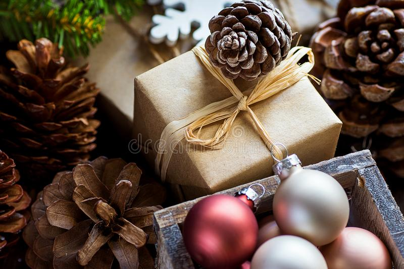 Stapel van Kerstmis en Nieuwjaargiftvakjes die in Ambachtdocument Kleurrijke van de Sparrentakken van Ballen Grote Denneappels Gr stock fotografie