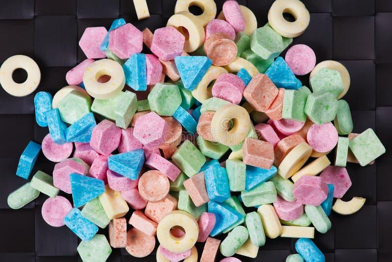 Stapel van kleurrijk zoet suikergoed op zwarte achtergrond royalty-vrije stock afbeeldingen