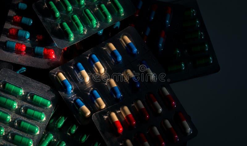 Stapel van kleurrijke capsulepillen in blaarpak op donkere achtergrond Drugsbeleid en begrotingen Antibiotisch druggebruik met re royalty-vrije stock foto's