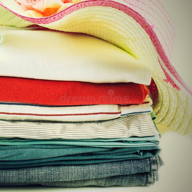 Stapel van kleurrijke kleren en Mooie de zomerhoed over witte bac stock afbeelding