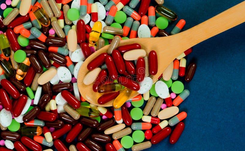 Stapel van kleurrijke tabletten en capsulespillen en houten lepel op blauwe achtergrond Antibiotisch weerstandsconcept farmaceuti royalty-vrije stock fotografie