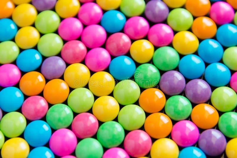 Stapel van kleurrijke zoete suikergoedchocolade met een laag bedekte achtergrond Colou royalty-vrije stock afbeeldingen