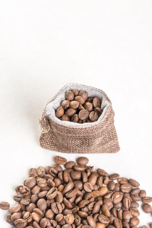Stapel van koffiebonen en jute drawstring zak op de witte achtergrond stock foto