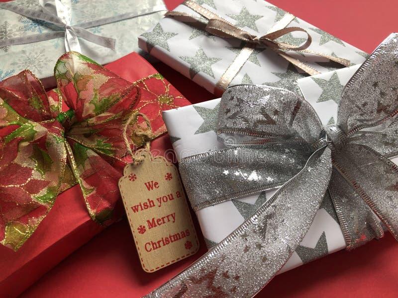 Stapel van luxe verpakte Kerstmisgiften op een rode achtergrond royalty-vrije stock afbeelding