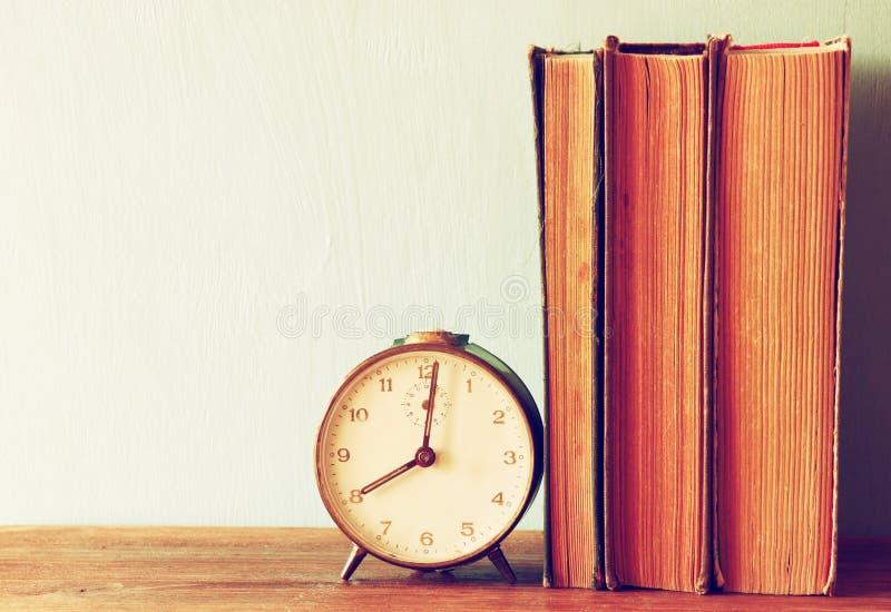 Stapel van oude boeken en oude klok over houten lijst Gefiltreerd beeld stock fotografie