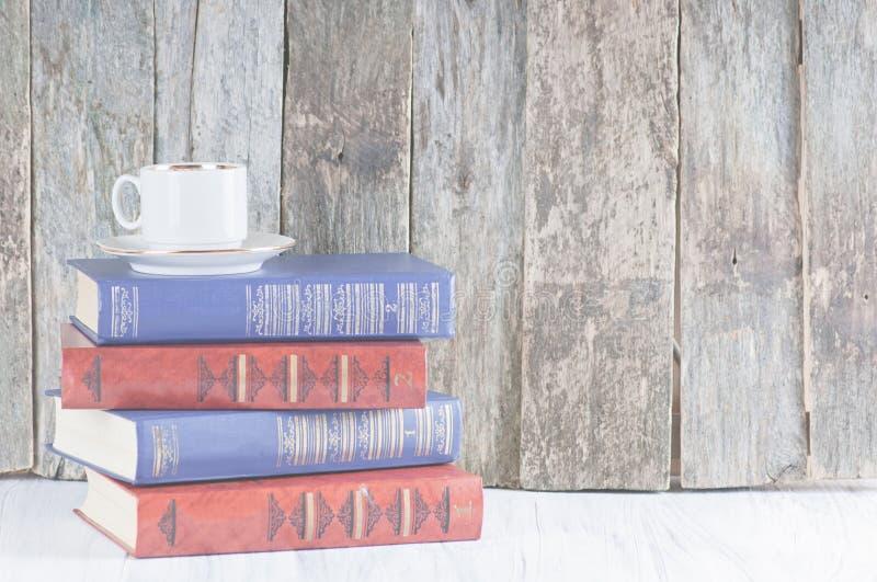 Stapel van oude boeken op een houten retro achtergrond en een witte worktop stock foto