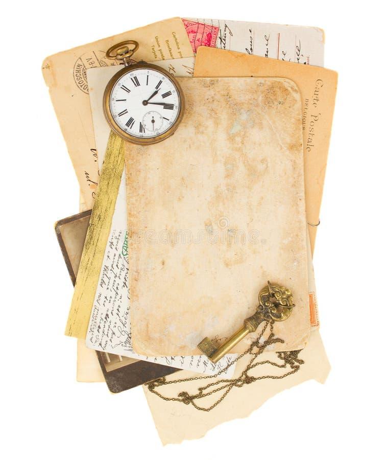 Stapel van oude foto's en documenten met antieke klok stock afbeeldingen