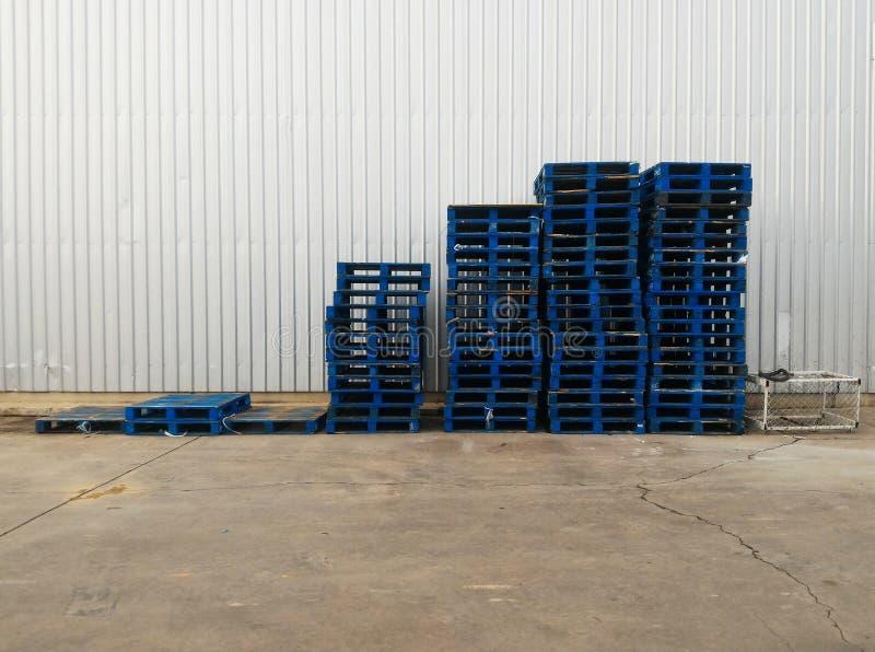 Stapel van oude houten pallet op vuile grond voor staalmuur in de industrie stock fotografie