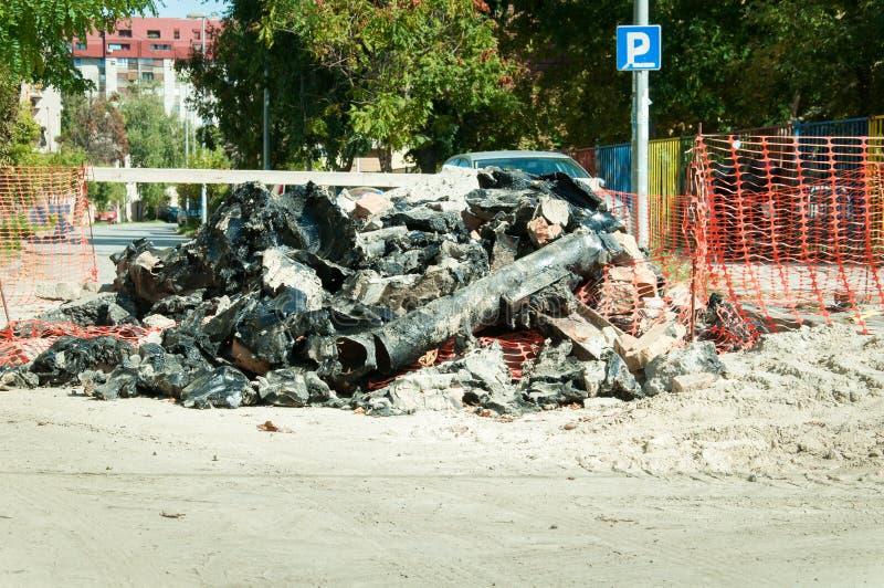 Stapel van oude pijpen op de straat die van de grond wordt opgegraven en die met nieuwe pijpleiding wordt vervangen royalty-vrije stock afbeelding