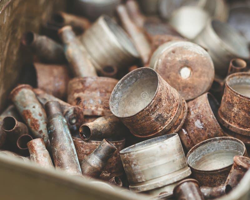 Stapel van oude roestige shell omhulsels van aanvalsgeweren en opgezette granaatlanceerinrichtingen in metaaldoos stock afbeelding