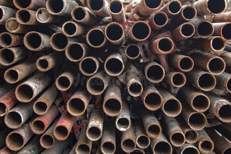 Stapel van ronde oude rode, bruine, roestige metaalpijpen Ruwe Oppervlaktetextuur stock fotografie