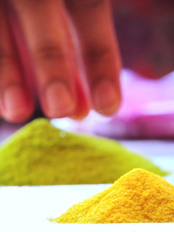 Stapel van twee trillende rangolikleuren of gekleurd zand, groen en geel met magenta op achtergrond samen met damehanden ongeveer stock foto's