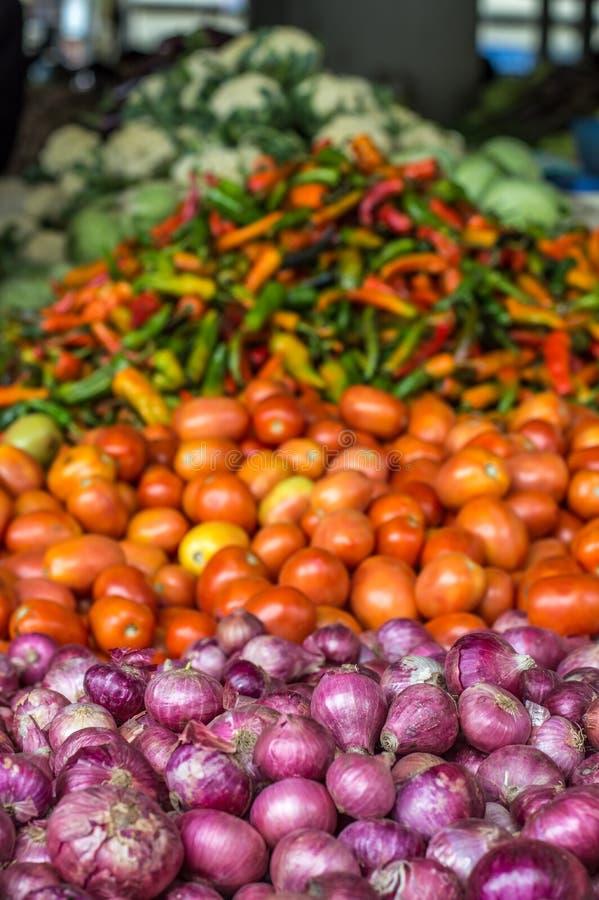 Stapel van uien naast een stapel van tomaten en peper royalty-vrije stock afbeelding