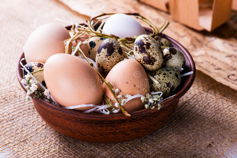 Stapel van verse kip en van kwartels eieren in een bruine kom royalty-vrije stock foto