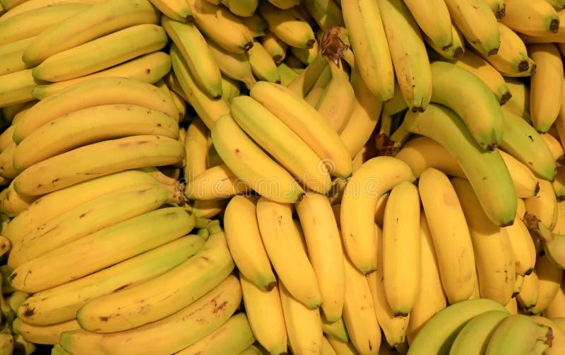 Stapel van verse rijpe bananen die in de markt verkopen stock foto's