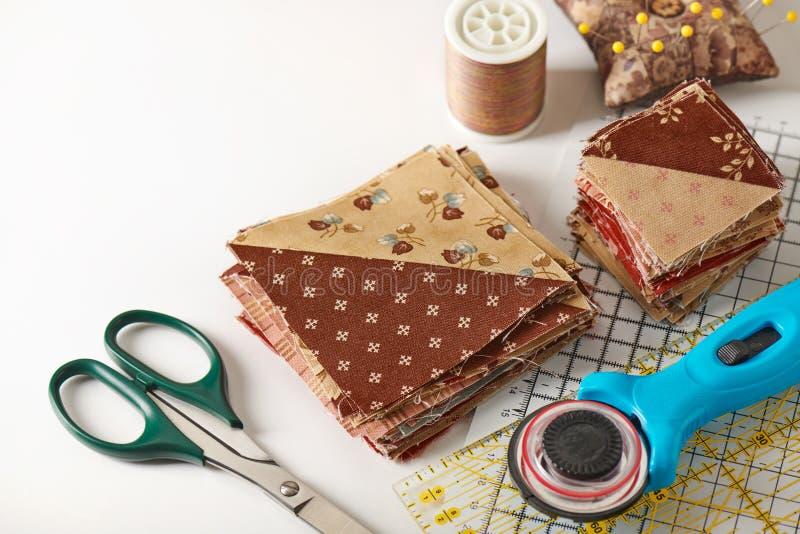 Stapel van vierkante die stukken van stof van driehoeksplakken wordt genaaid, traditioneel lapwerk, naaiende toebehoren stock afbeelding