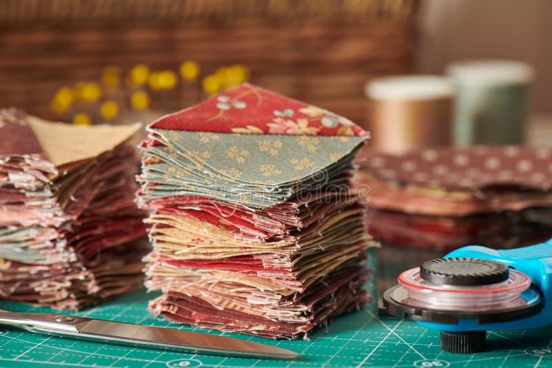 Stapel van vierkante die stukken van stof van driehoeksplakken wordt genaaid, traditioneel lapwerk, naaiende toebehoren stock foto's