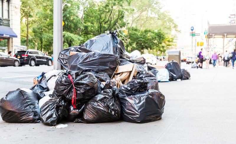 Stapel van vuilniszakken op stadsstraat stock afbeeldingen