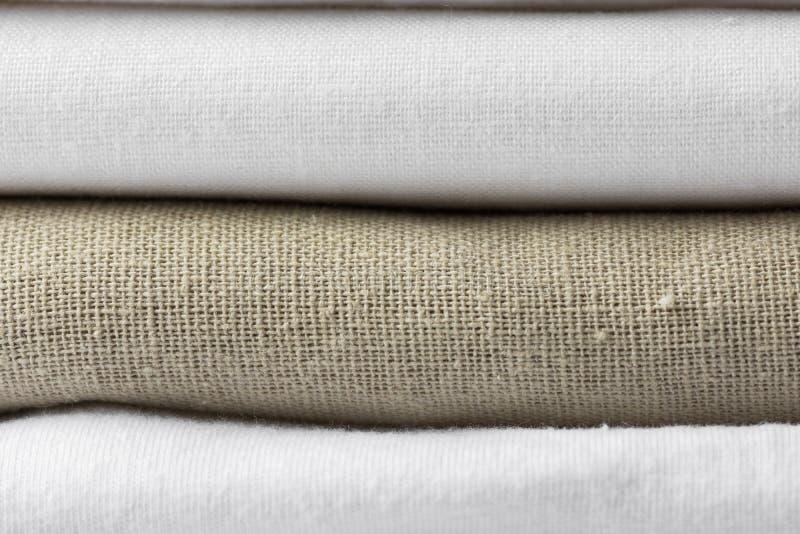 Stapel van wit en beige zuiver organisch katoen en linnen gevouwen stof Het huis textielconcept van de kledingswasserij stock fotografie