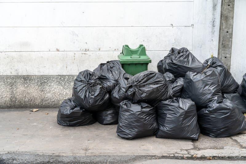 Stapel van zwart huisvuil op het voetpad bij zijweg in grote stad, stock foto's