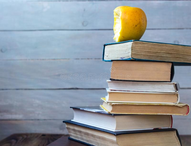 Stapel von alten Büchern und von gebissenem Apfel lizenzfreie stockbilder