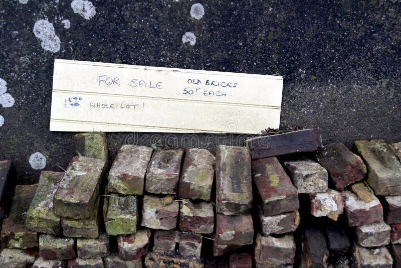 Stapel von alten benutzten aufbereiteten Hausziegelsteinen mit a für Verkaufszeichen stockbild