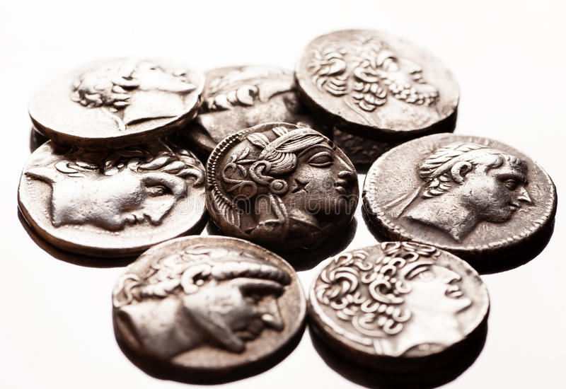 Stapel von altgriechischen Münzen auf reflektierender Oberfläche lizenzfreie stockfotografie