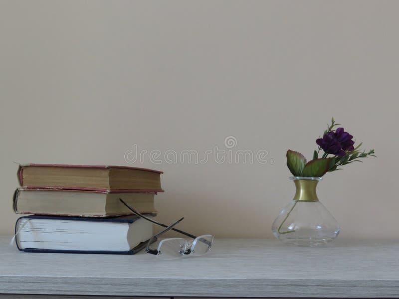 Stapel von Büchern, ein Paar Gläser und Blumen stockbilder